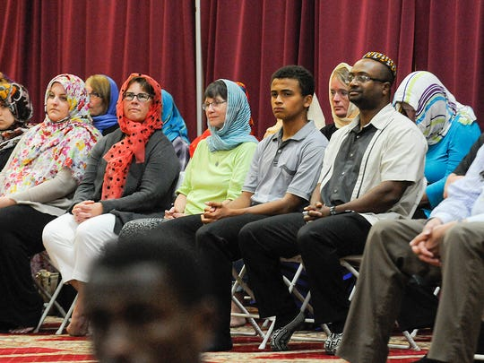 Community members watch from the back of the the worship space as Muslim men do their evening prayers Thursday, June 23 at the Islamic Center in St. Cloud.