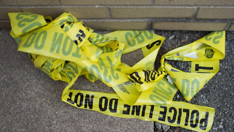 Remnants of crime scene tape remain on the ground in