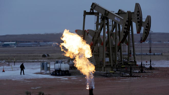 In this Oct. 22, 2015 file photo, workers tend to oil pump jacks behind a natural gas flare near Watford City, N.D.