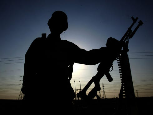 An Iraqi soldier is seen in silhouette as he guards the main check point of Fallujah in January 2005.