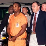 Serial killer suspect Derrick Todd Lee (center) is escorted by Baton Rouge Sheriff Captain Duane Jones (right) and Captain Willie Douglas (left) to his court appearance in a Baton Rouge courtroom on Wednesday morning July 2, 2003.
