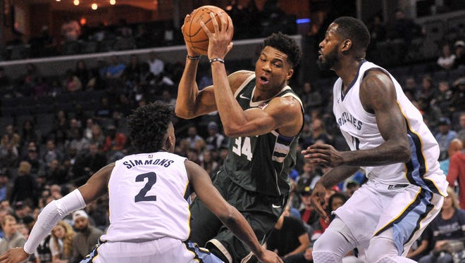 Bucks forward Giannis Antetokounmpo tries to go between Kobi Simmons (2) and JaMychal Green of the Grizzlies on a drive to the basket on Monday night in Memphis.