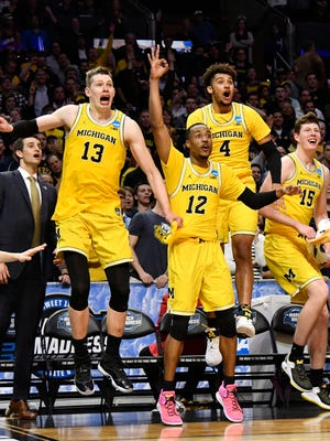 Michigan Wolverines forward Moritz Wagner (13) and guard Muhammad-Ali Abdur-Rahkman (12) and forward Isaiah Livers (4) and center Jon Teske (15) celebrate after defeating the Texas A&M Aggies in the semifinals of the West regional of the 2018 NCAA Tournament.