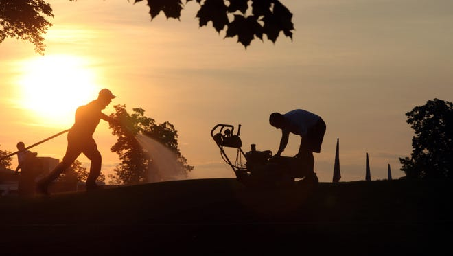 The grounds crew groom the golf course as the sun comes up at the KPMG Women's PGA Championship at the Westchester Country Club in Harrison, June 12, 2015.