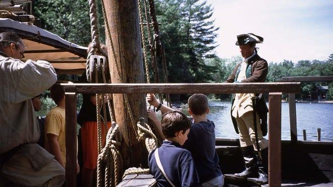 Visitors talk with reenactors aboard replica 1776 gunboat Philadelphia II at Lake Champlain Maritime Museum.