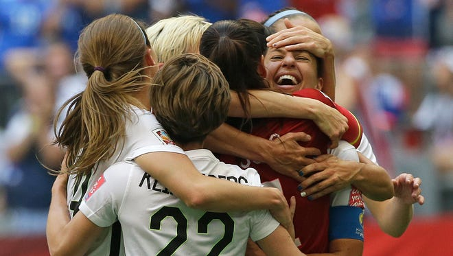 United States' Carli Lloyd, right, celebrates with teammates after Lloyd scored her third goal against Japan during the first half of the FIFA Women's World Cup soccer championship Sunday in Vancouver, British Columbia, Canada.
