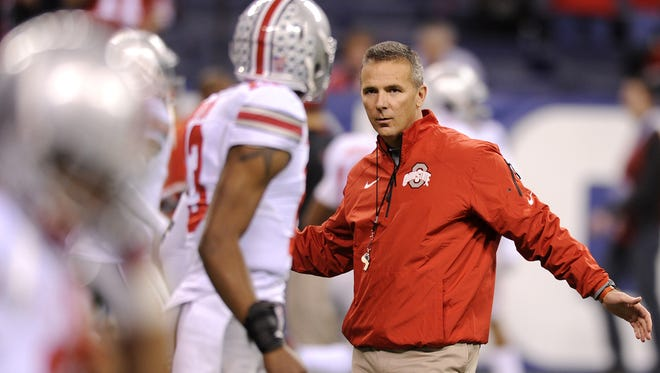 Ohio State head coach Urban Meyer talks to his players during warm-ups prior to the start of the Big Ten Championship game against Michigan State, Saturday, December 7, 2013, at Lucas Oil Stadium.