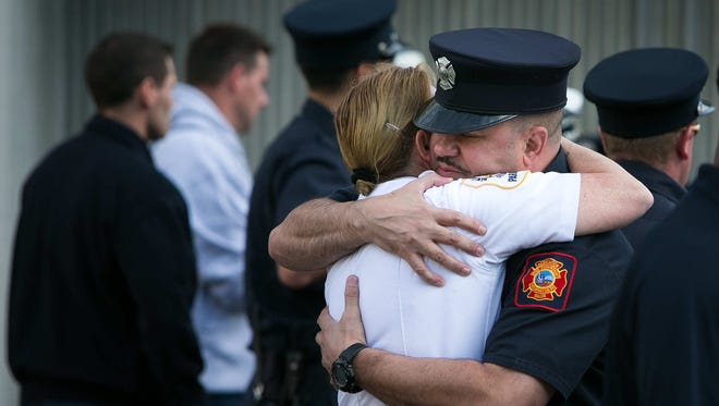 Firefighters console one another after the bodies of Lt. Christopher Leach and Senior Firefighter Jerry Fickes was transported from the Delaware Medical Examiner's Office to their respective funeral homes Monday, Sept. 26, 2016.