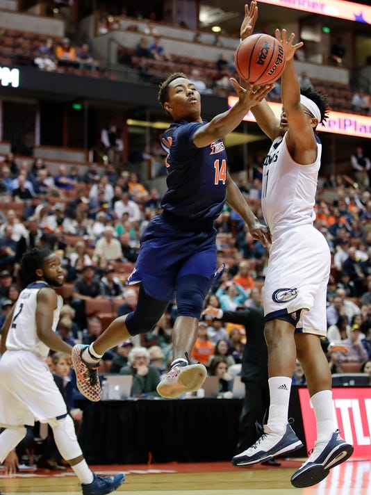 Cal State Fullerton's Khalil Ahmad, center, goes up for a basket past UC Davis's Chima Moneke during the first half of an NCAA college basketball game at the Big West men's tournament Friday, March 10, 2017, in Anaheim, Calif. (AP Photo/Jae C. Hong)