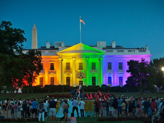 People gather to see the White House illuminated with