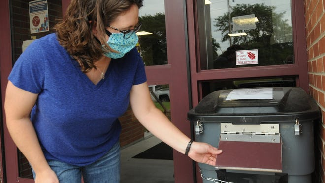 USD 305 parent Anne Hoekstra, of Salina, opens the flap to the facial mask donation tub at Salina Public Schools District Offices, 1511 Gypsum St., on Wednesday.