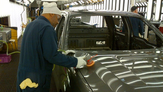 A worker at Ford's truck plant in Dearborn, Mich., buffs out paint flaws discovered by a special 3-D scanner.