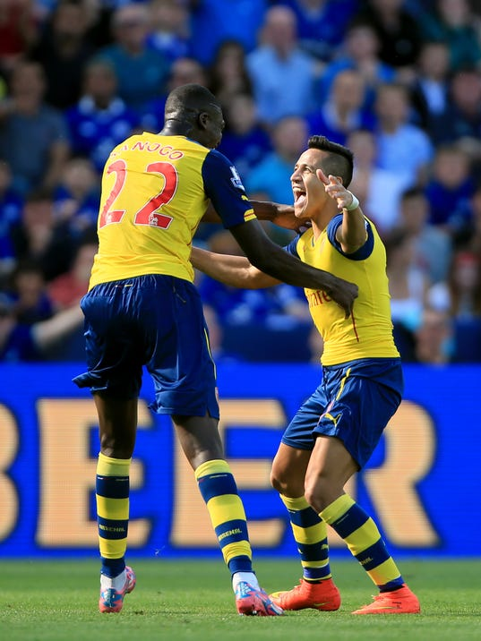 Arsenal's Alexis Sanchez, right, celebrates scoring his side's first goal of the game with teammate Yaya Sanogo during their English Premier League soccer match against Leicester City at the King Power Stadium, Leicester, England, Sunday, Aug. 31, 2014. (AP Photo/Nick Potts, PA Wire)     UNITED KINGDOM OUT    -   NO SALES   -   NO ARCHIVES