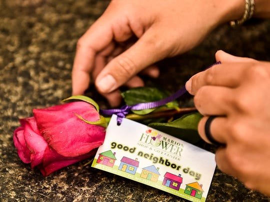 Tags are tied onto the stems of the roses that will be used in the Good Neighbor Day event. The event, held by the Marion Flower Shop is meant to get people in the community to interact and open up a dialogue between them.