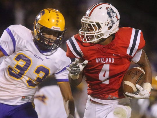Oakland's Lazarius Patteron (4) runs the ball as Smyrna's Tevin Shipp (33) moves in for a tackle, on Friday, Oct. 28, 2016, at Oakland.