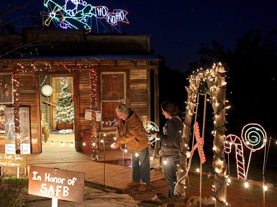 Jill Avis (left) and Jennica Lambert check the lights in the Santa's Workshop display during ElectriCritters at River Bend Nature Center in this file photograph. The annual event starts Nov. 18.