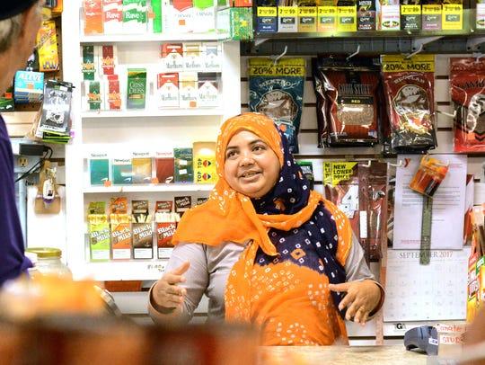 Kamrun Nahar of Halal Meat and Grocery, center, talks