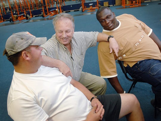 Former Wayne County football standout Jerrell Powe (right) and his mentor Joe Barnett (center) chat with Wayne County defensive coordinator Kelly  Morphy while visiting Powe's old school on Thursday.