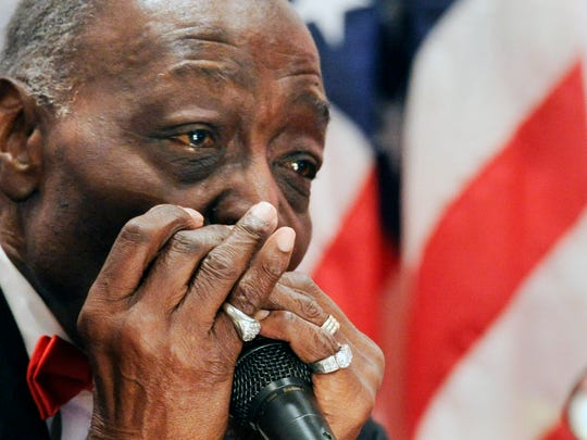 """Voni Grimes comes to the altar and plays """"May the Work I've Done Speak For Me"""" on his harmonica during a program honoring the life and work of Voni and Lorrayne Grimes at Small Memorial A.M.E Zion Church in York Sunday November 30, 2014."""