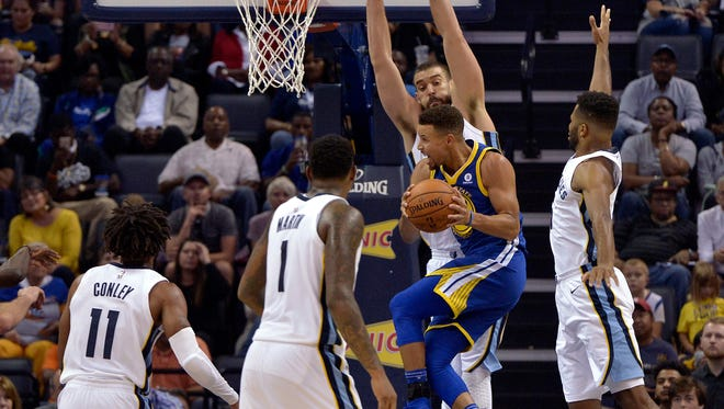 Warriors guard Stephen Curry jumps to pass the ball between Grizzlies guard Mike Conley (11), forward Jarell Martin (1), center Marc Gasol and guard Andrew Harrison (5) during the second half Saturday.