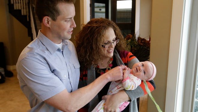 """Preston """"Pret"""" and Megan Dahlgren hold their daughter Naomi as they pose for a photograph Monday, Jan. 5, 2015, near Salt Lake City. Two Utah men set to appear in the reality TV show """"My Husband's Not Gay,"""" say they're fulfilled in their relationships to their wives even though they're attracted to other men. The show's concept has come under fire since it was announced by the TLC network last month."""