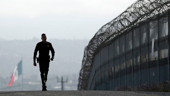In this June 22, 2016 photo, Border Patrol agent Eduardo Olmos walks near the secondary fence separating Tijuana, Mexico, background, and San Diego in San Diego. U.S. President Donald Trump will direct the Homeland Security Department to start building a wall at the Mexican border.
