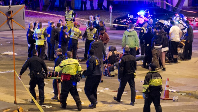 In this March 12, 2014, file photo, paramedics transport a person who was struck by a car on Red River Street in downtown Austin, Texas, during the South by Southwest music festival. An Austin police officer who worked security at last year's festival on Monday, Nov. 2, 2015, described the chaotic scene when a speeding car plowed into a crowd of people, leaving four dead and more than 20 hurt.