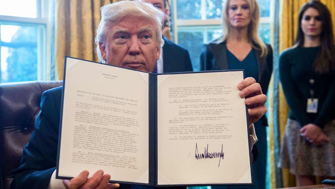 President Trump shows one of the directives he signed in the Oval Office at the White House on Jan. 24, 2017.