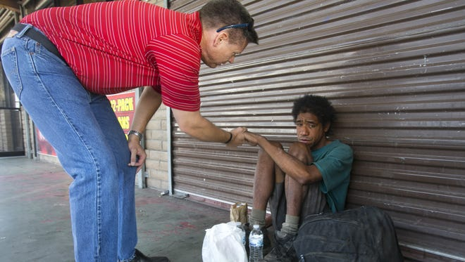 """Cliff Danley, a chaplain and the """"Hope Coach"""" coordinator with Phoenix Rescue Mission, shakes the hand of homeless man, Michael Gallegos after giving him bottled water and a bagged lunch on the streets in Phoenix in May 2013."""