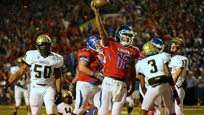 Cooper quarterback Lorenzo Joe (12) celebrates after scoring a touchdown in the first quarter of the Cougars' 56-31 win on Friday, Oct. 4, 2013, at Shotwell Stadium.