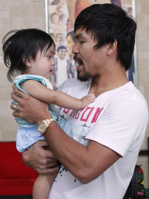 Filipino boxing star Manny Pacquiao, shown holding his youngest child Israel in February, will move his family into their new house in Los Angeles befofre his May 2 superfight against Floyd Mayweather.