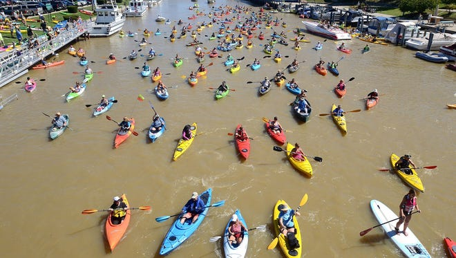 In this September 2014 photo, kayakers head west on the Black River in the annual Paddle and Pour event in Port Huron.