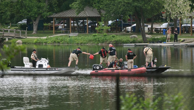 Washtenaw County Sheriffs hand off a gas can to rescue crews while searching the Huron River near Argo Park in Ann Arbor for a man reported to havejumped in the water and disappeared, Wednesday, May 30, 2018.