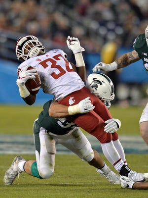 Washington State Cougars running back James Williams (32) is hit by Michigan State Spartans linebacker Joe Bachie (35) during the third quarter in the 2017 Holiday Bowl at SDCCU Stadium.