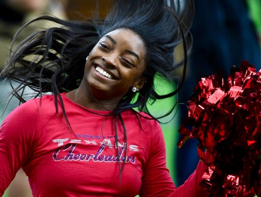 Olympic athlete Simone Biles warms up before the game