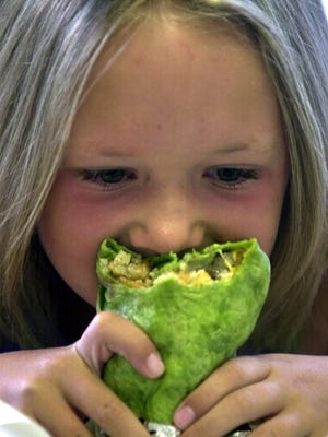 Fort Collins resident Kaley Smylie digs into a Big City Burrito in this 2002 file photo.