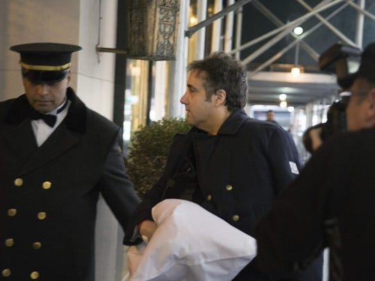 """Michael Cohen arrives at his home in New York with his left arm in a sling supported by a pillow Friday, Jan. 18, 2019. Democrats are vowing to investigate whether President Donald Trump directed Cohen, his personal attorney, to lie to Congress about a Moscow real estate project, calling that possibility a """"concern of the greatest magnitude."""" (AP Photo/Kevin Hagen)"""
