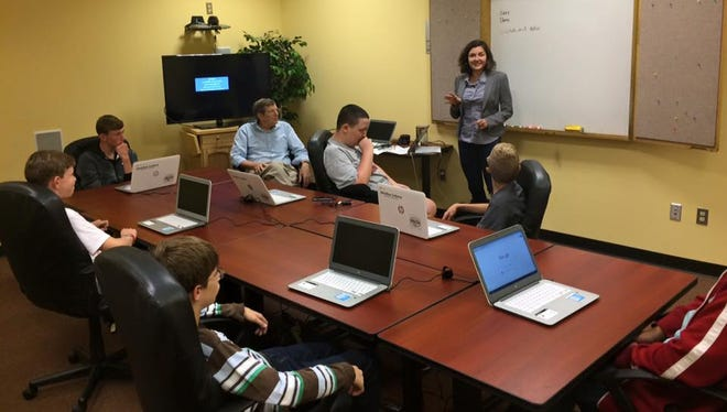 Participants in the first Greenhouse Coding Academy listen to Elena Sergienkov.