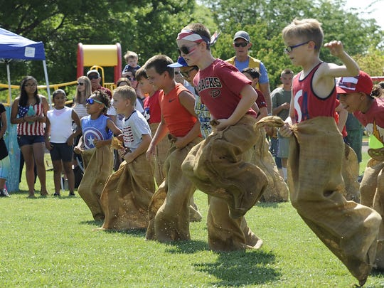 A crowd cheers on a group of boys as they compete in a sack race.