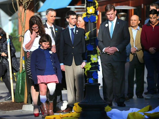 Boston Mayor Marty Walsh, right. looks down after Boston Marathon survivor Jane Richard, left, and her brother Henry removed a drape covering a memorial honoring victims and survivors at one of two blast sites near the finish line of the Boston Marathon in Boston, Wednesday, April 15, 2015.