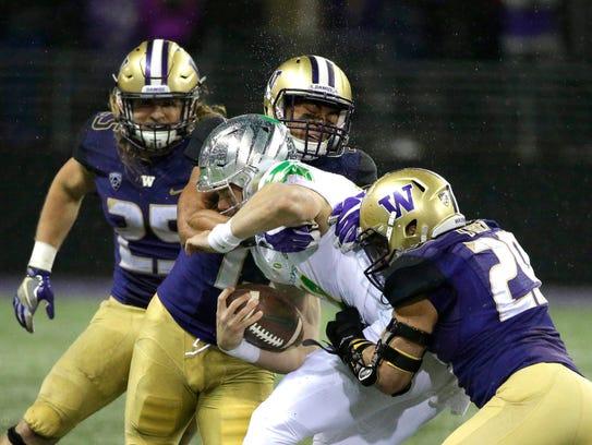 Oregon quarterback Braxton Burmeister is tackled by