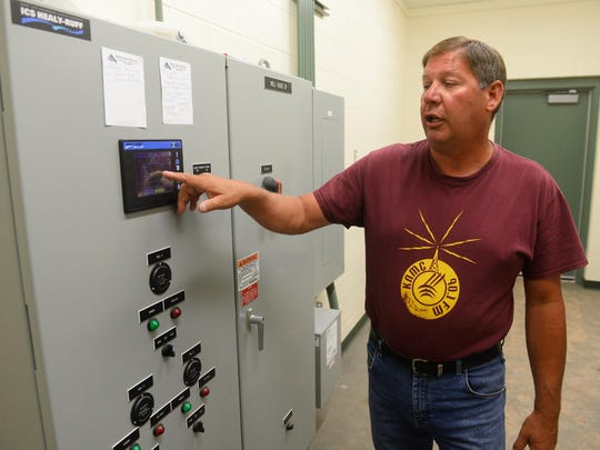 Kent Luoma, president of the Sand Coulee Water Board, explains the computerized controls in the town's new pump house.
