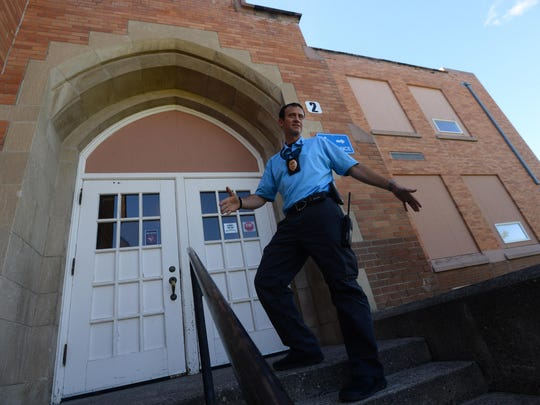 School Resource Officer Aaron Frick stands at the main entrance of Roosevelt Elementary School. He discusses safety concerns in some the district's aging school buildings, including these steps that are the only public entrance into the building. They are hollow and become icy in winter.