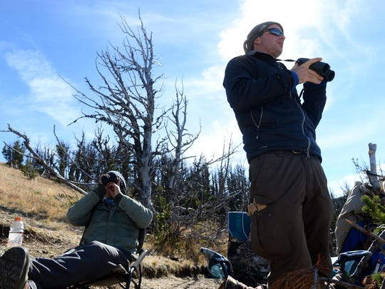 Jeff Grayum, left, and Ronan Dugan look for migrating raptors from their observation station in the Big Belt Mountains. They are counting raptors including golden eagles as part of a migrating raptor survey.