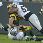 Aug 22, 2014; Green Bay, WI, USA; Oakland Raiders defensive end LaMarr Woodley (57) and linebacker Nick Roach (53) pressure Green Bay Packers quarterback Aaron Rodgers (12) at Lambeau Field. Mandatory Credit: Kirby Lee-USA TODAY Sports