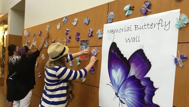 Three officers of the LSUA Psychology Club adjust butterflies representing suicides. They make up a Memorial Butterfly Wall intended to raise awareness of the prevalence of suicide in Central Louisiana and across the nation.