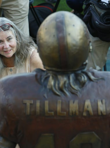"Pat Tillman's  mother Mary ""Dannie"" Tillman hugs her granddaughter (not allowed to use name) as she looks up at a statue in her son's likeness during an unveiling ceremony at Sun Devil Stadium Wednesday, Aug. 30, 2017, in  Tempe.  Ariz."