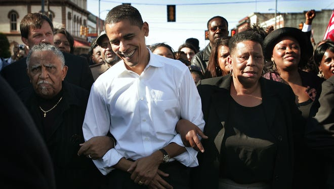 """Then-senator Barack Obama marches with a crowd to the Edmund Pettus Bridge to commemorate the 1965 """"Bloody Sunday"""" voting rights march anniversary on March 4, 2007, in Selma, Ala."""