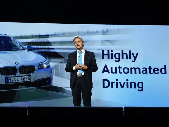 BMW executive Elmar Frickenstein speaks to a crowd