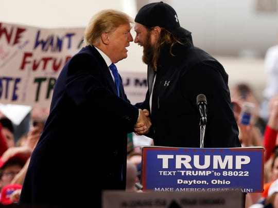 Then-Republican presidential candidate Donald Trump shakes hands with former Ohio State and NFL football player Nick Mangold as he arrives for a rally on March 12, 2016, in Vandalia, Ohio.